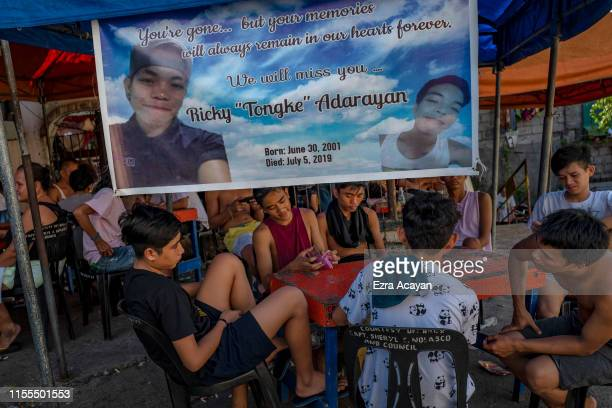 Relatives and neighbors play card games to raise money for funeral expenses at the wake of Ricky Adarayan on July 13 2019 in Malabon Metro Manila...