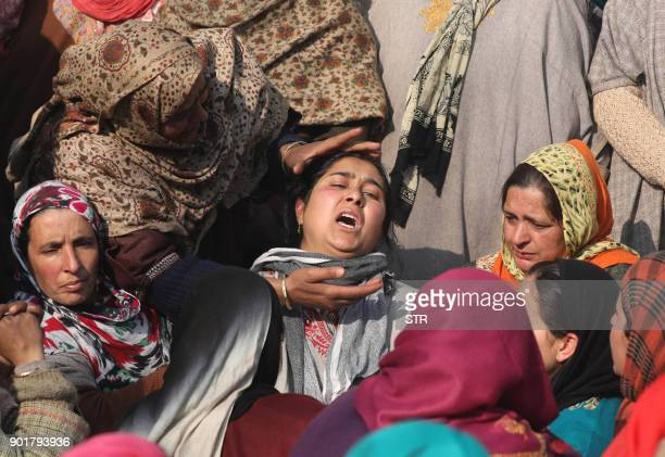 Relatives and neighbours of slain Indian policeman Ghulam Nabi react during his funeral procession at village Rohama Rafiabad some 70 kms north of...