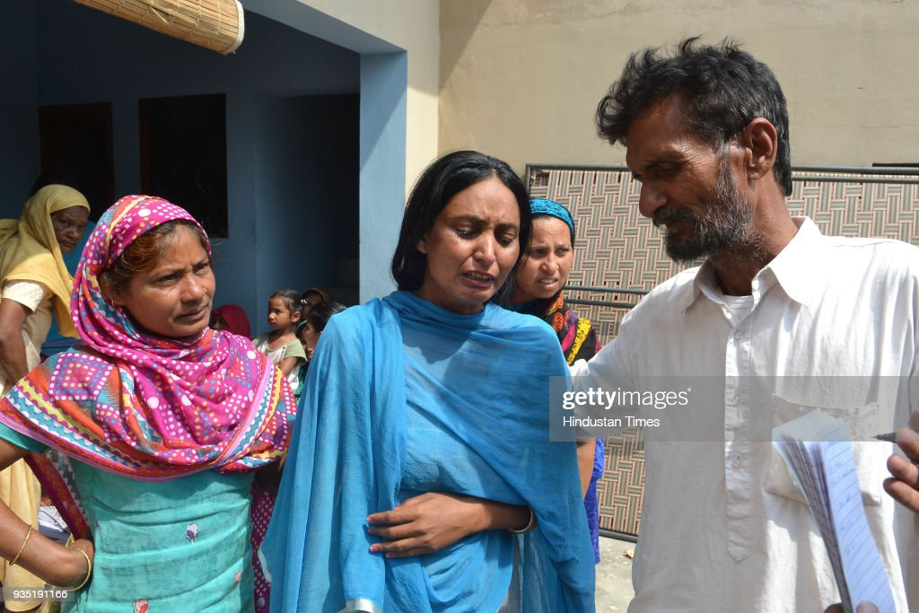 Relatives and neighbours of Surjit Singh consoling his wife Usha at their residence in village Chuharwali on March 20 2018 near Jalandhar India The...