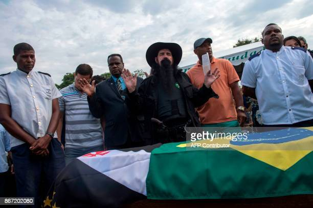 Relatives and police officers pray during the funeral of police colonel Luis Gustavo Teixeira in Sulacap in western Rio de Janeiro Brazil on October...