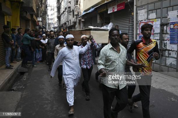 Relatives and residents carry the coffin of a fire victim during a funeral procession after a fire tore through apartment blocks in Bangladesh's...