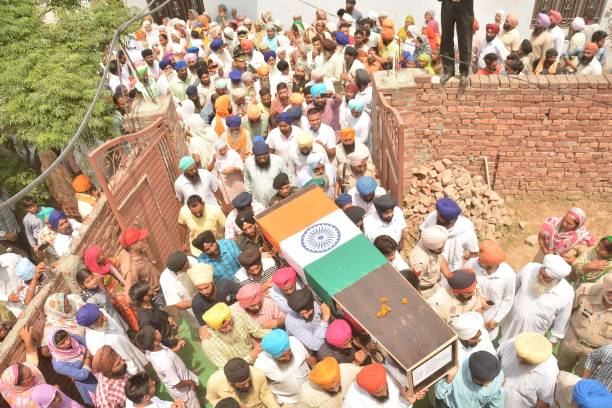 Relatives and residents carry the coffin of Indian Army soldier Paramjit Singh ahead of his funeral at Vein Pein village some 45 km from Amritsar on..