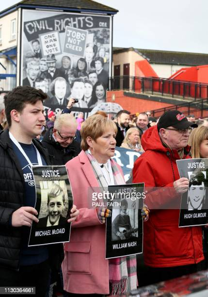 Relatives and supporters of the victims of the 1972 Bloody Sunday killings hold images of those who died as they march from the Bogside area of Derry...