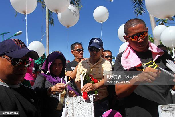 Relatives and supporters of the victims of the infamouse Maguindanao massacre including Governor Ismael Mangudadatu light candles as they offer...