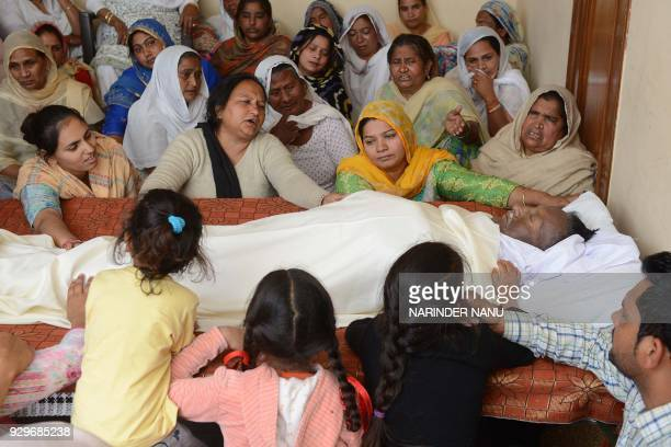 Relatives and Surjit Kaur wife of the Sufi singer Pyare Lal Wadali mourn at a cremation ground on the outskirts of Amritsar on March 9 2018 Famous...
