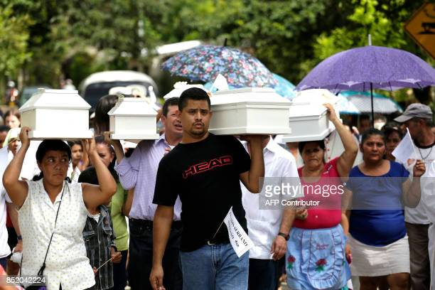 Relatives and villagers hold a funeral to bury the exhumed and identified remains of six children killed during El Salvador's 19801992 civil war in...