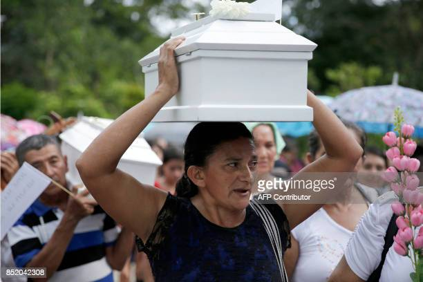 Relatives and villagers hold a funeral to bury the exhumed and identified remains of six children killed during El Salvador's 1980-1992 civil war, in...