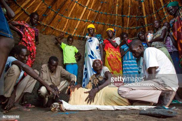 TOPSHOT Relatives assist Nyanom Gay a 26yearold mother of four after being infected with malaria in Padding near Lankien Jonglei South Sudan on July...