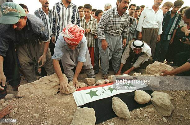 Relatives bury a child who allegedy died in a USBritish airstrike June 20 2001 at cemetery in Tall Afar northern Iraq 23 people were killed and...