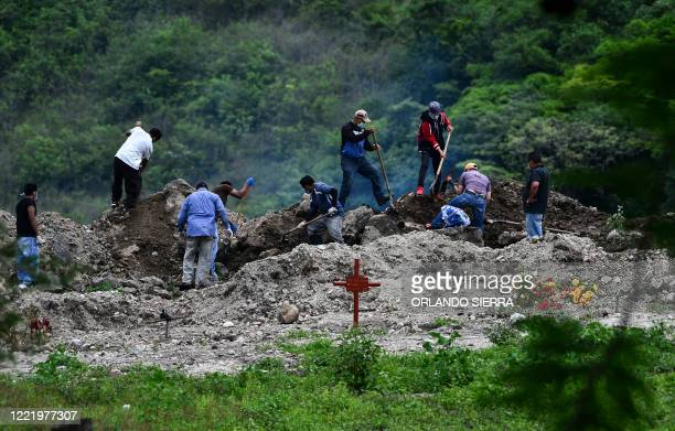 Relatives bury an alleged victim of the new coronavirus at the Parque Memorial Jardin de los Angeles cemetery, 14 km north of Tegucigalpa, on June...
