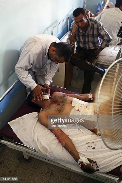 Relatives care for a man laying in the hospital who was injured when a suicide car bomb exploded outside a police recruiting center July 28 2004 in...