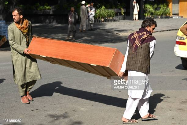 Relatives carry a coffin to receive the dead body of a victim of the August 26 twin suicide bombs, which killed scores of people including 13 US...