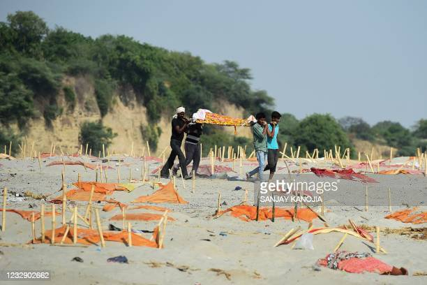 Relatives carry a dead body past shallow graves covered with saffron clothes of suspected Covid-19 coronavirus vicitims near a cremation ground on...