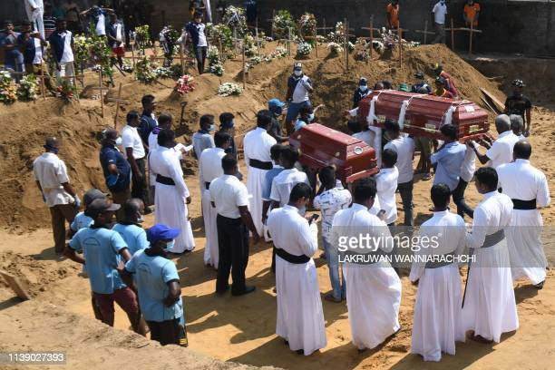 Relatives carry coffins of bomb blast victims for a burial ceremony at a cemetery in Negombo on April 24 three days after a series of suicide attacks...