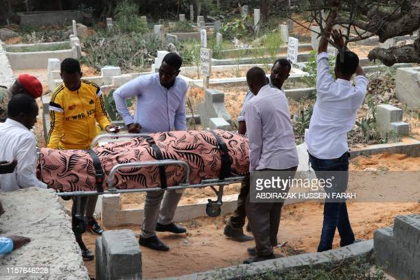 Relatives carry on July 25 2019 the dead body of one of Mogadishu district commissioners who was killed in a suicide bomb attack on July 24 Six...