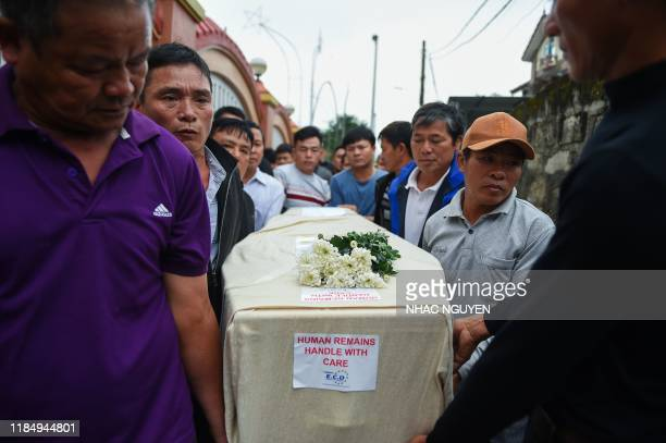 Relatives carry the casket bearing the body of Nguyen Van Hung on arrival at Dien Chau district Nghe An province on November 27 2019 after being...