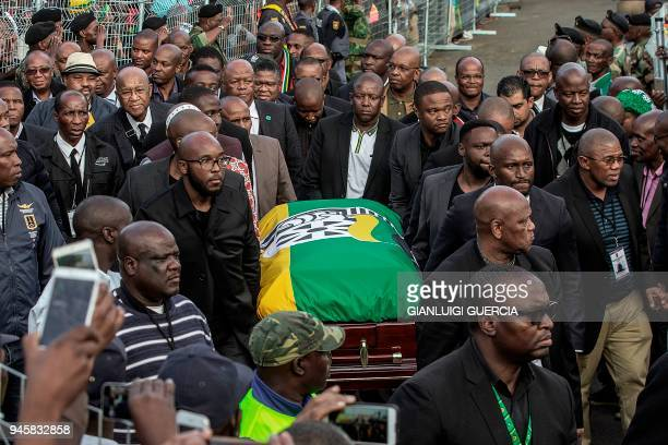 Relatives carry the casket containing the body of the late Winnie Mandela at her house in Soweto in Johannesburg on April 13 2018 Winnie Mandela died...