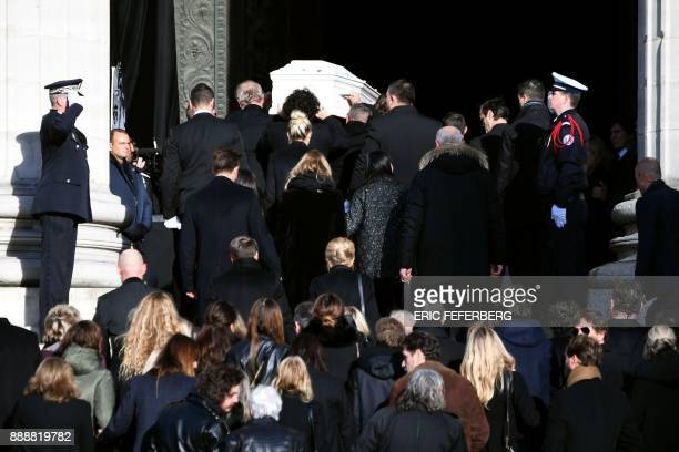 Relatives carry the coffin inside the La Madeleine Church prior to the funeral ceremony in tribute to late French singer Johnny Hallyday on December...