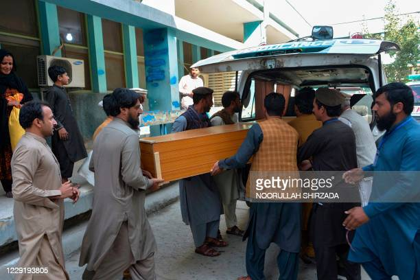 Relatives carry the coffin of a victim, who was killed in a stampede, outside a mortuary in Jalalabad on October 21, 2020. - At least 11 women were...