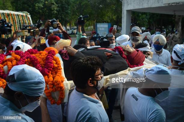 Relatives carry the dead body of track legend Milkha Singh, who died aged 91 following a long battle with Covid-19, during the cremation ceremony in...