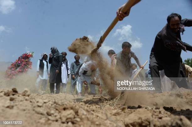 Relatives colleagues and friends of AFP driver Mohammad Akhtar take part in a burial ceremony in Kabul on July 23 a day after he was killed in a...