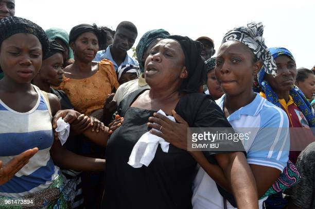 Relatives cry as they mourn during a funeral service for 17 worshippers and two priests who were allegedly killed by Fulani herdsmen at...
