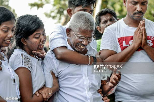 Relatives cry at the graveside during the funeral of a victim of the Easter Sunday Bombings at a local cemetery on April 24 2019 in Colombo Sri Lanka...