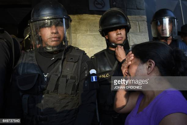 Relatives cry outside the children's shelter Virgen de la Asuncion guarded by police after a fire at the facility killed at least 19 people in San...