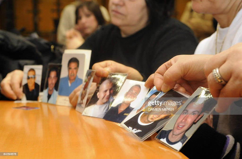 Relatives display photos of seven worker : News Photo