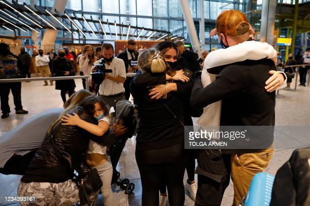Relatives embrace as they arrive from the United States at Heathrow's Terminal 5 in west London on August 2, 2021 as quarantine restrictions ease. -...