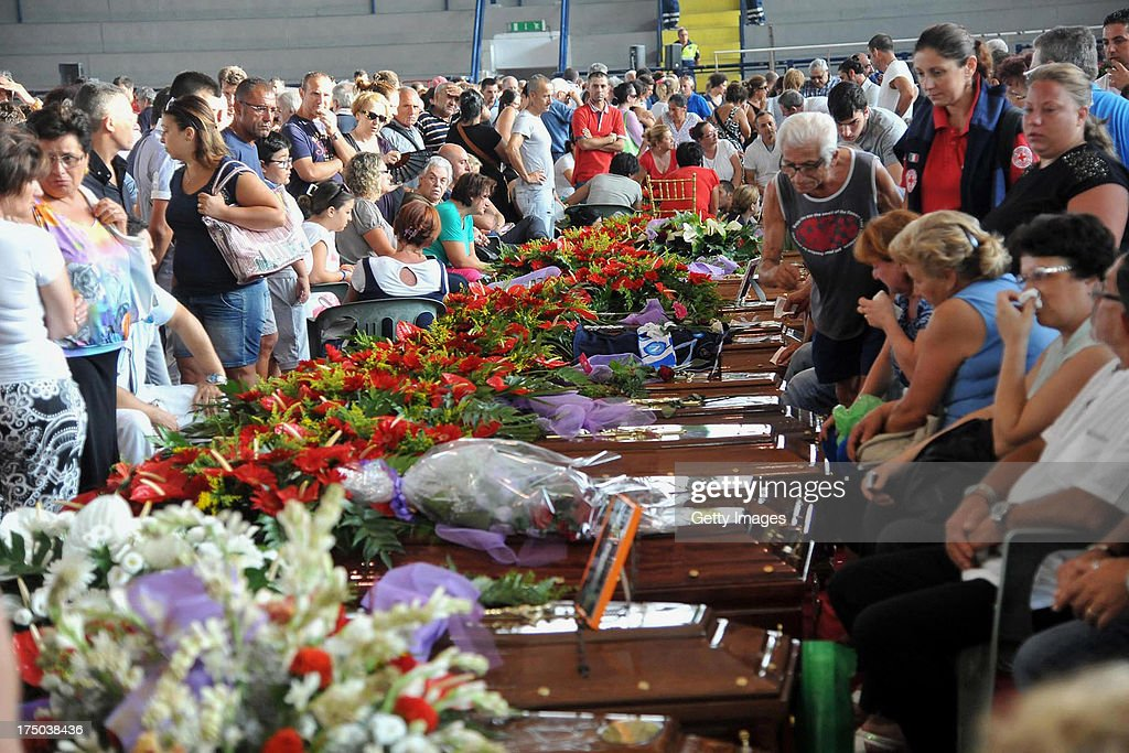 Relatives gather to grieve near to the coffins of the victims of the Monteforte Irpino coach crash during the funeral held at a local indoor sports arena on July 30, 2013 in Pozzuoli, Italy. In the second major European transport disaster in a week, 38 people were killed when a coach bus fell from a viaduct near Monteforte Irpino, Italy on July 28.