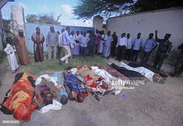 Relatives gather to look at the dead bodies of ten people including children after a raid on their farms in Bariire some 50 km west of Mogadishu on...