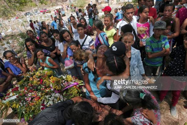 TOPSHOT Relatives grieve during the funeral of some of the victims of the prison fire in Valencia northern Carabobo state Venezuela March 30 2018 A...