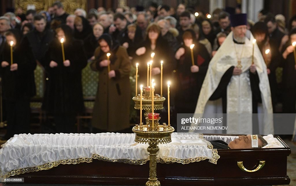Relatives hold candles in front of the casket of slain Russian ambassador to Turkey Andrei Karlov during the funeral ceremony at the Christ the Savior Cathedral in Moscow on December 22, 2016. President Vladimir Putin on December 22, 2016 bade farewell to Andrei Karlov at a packed memorial ceremony in Moscow for the diplomat who was assassinated in Turkey by an off-duty policeman. / AFP / Alexander NEMENOV