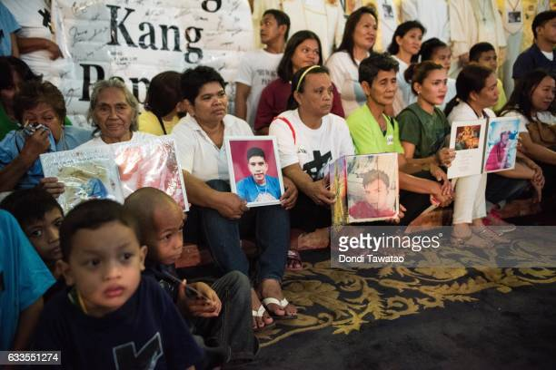 Relatives hold pictures of their loved ones killed during a mass held for victims of the drug war on February 2 2017 in Manila Philippines Philippine...