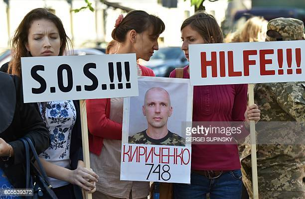 Relatives hold placards reading 'SOS' and 'Help' during a rally demanding the release of Ukrainian servicemen captured and prisoned by proRussian...
