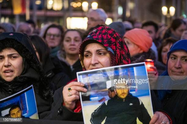 Relatives hold up photos of the victims at a vigil near the Midnight shisha bar, one of the sites of last night's shootings, on February 20, 2020 in...