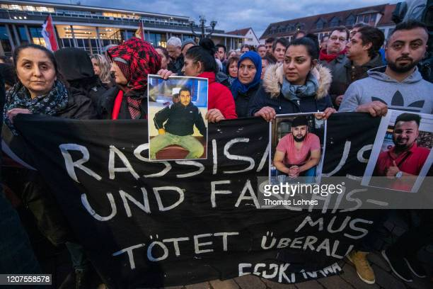 Relatives hold up photos of the victims at a vigil near the Midnight shisha bar one of the sites of last night's shootings on February 20 2020 in...