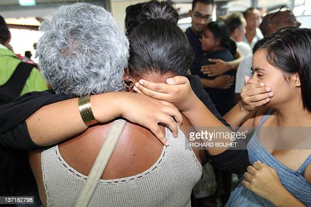 Relatives hug each other upon the arrival of the 31 passengers who survived the Costa Concordia accident early on January 16 2012 at the Saint Denis...