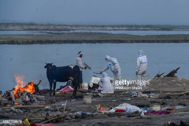 Relatives in personal protective equipment suits perform the last rites before the cremation of their loved one, who died due to the Covid-19...
