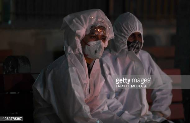 Relatives in personal protective equipment suits watch the cremation of their loved one who died of the Covid-19 coronavirus at Nigambodh Ghat...