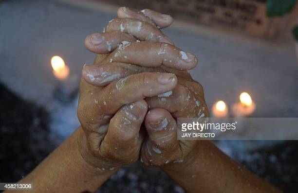 Relatives light candles offer flowers and say prayers at the tomb stone of their departed love ones at a cemetery in Manila on November 1 2014...