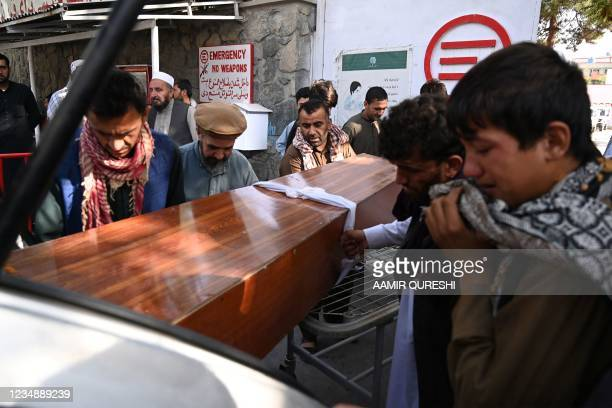 Relatives load in a car the coffin of a victim of the August 26 twin suicide bombs, which killed scores of people including 13 US troops outside...