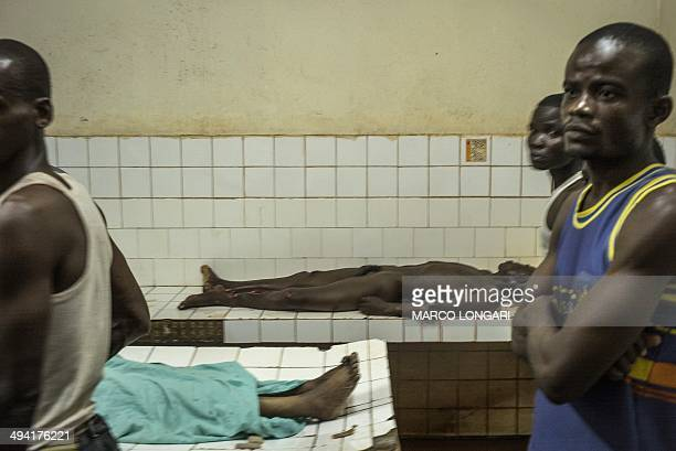 Relatives look on as two bodies are prepared in the morgue of the General Hospital in Bangui on May 28 2014 after ten people were killed and several...