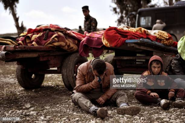 TOPSHOT Relatives mourn as bodies of Iraqi residents of west Mosul killed in an airstrike targeting Islamic State group jihadists are placed and...