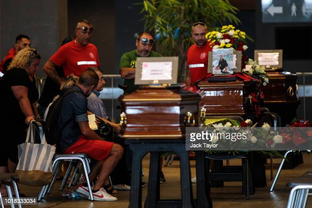 Relatives mourn by coffins of the victims of the Morandi Bridge disaster at the Fiera di Genova exhibition centre ahead of a state funeral service on...