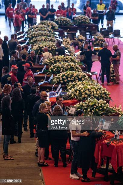 People look on during a State funeral service held for the victims of the Morandi Bridge disaster at the Fiera di Genova exhibition centre on August...