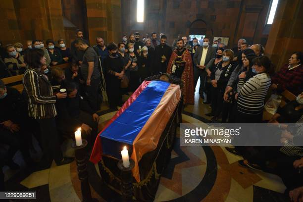 Relatives mourn by the coffin of an Armenian soldier killed in the fighting between Armenia and Azerbaijan over the breakaway region of...
