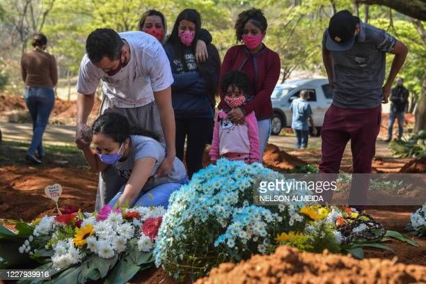 Relatives mourn during the burial of 65yearold Maria Joana Nascimento who died suspectedly from the new coronavirus at Vila Formosa Cemetery in the...
