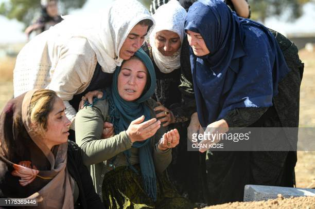 Relatives mourn in front of the grave of Halil Yagmur who was killed in a mortar attack a day earlier in Suruc near northern Syria border, during...